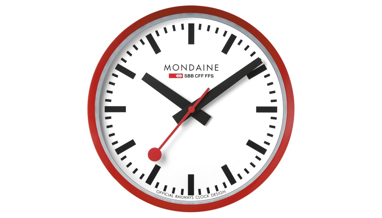 SBB wall clock from Mondaine. The legendary clock is a stylish accessory for the home, hotel lobbies, restaurants, offices... The clock has a white face and contains a quartz movement. Its red housing is made of aluminium and has a diameter of 25 centimetres. It is covered by crystal glass and is dust tight.