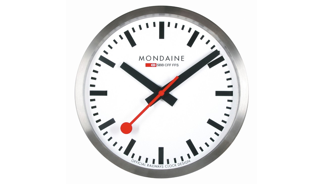 SBB wall clock from Mondaine. The legendary clock is a stylish accessory for the home, hotel lobbies, restaurants, offices... The clock has a white face and contains a quartz movement. Its housing is made of brushed aluminium and has a diameter of 25 centimetres. It is covered by crystal glass and is dust tight.