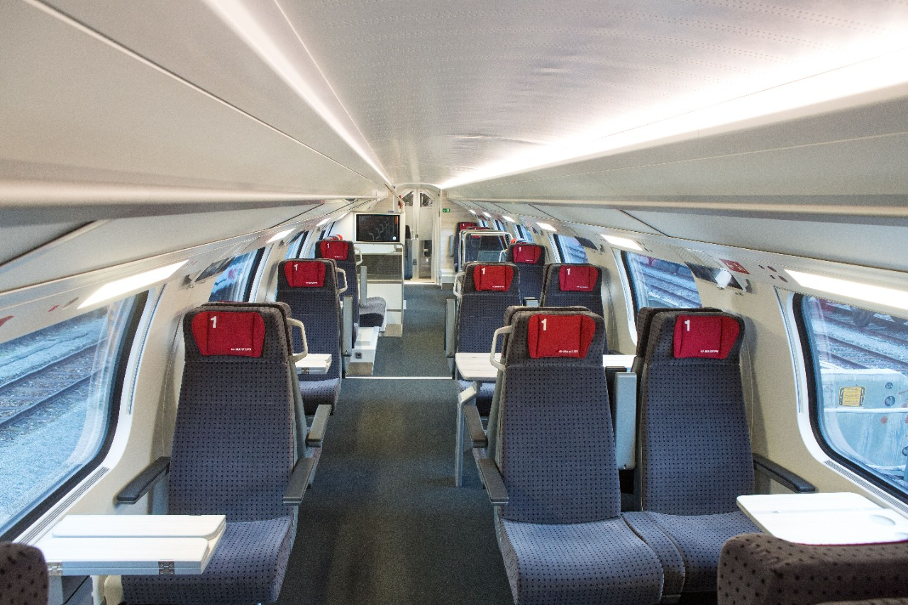 1st class interior – to the right of the aisle there are compartments to seat four and to the left there are compartments to seat two. The seat cushions are dark grey with a small red pillow attached to the headrest.