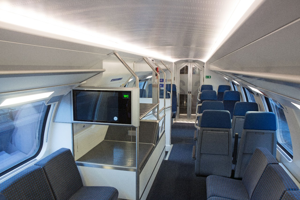 2nd class interior – the seat cushions are dark blue. On the left-hand side of the aisle there is an information screen and luggage stowage, beyond which are the stairs to the lower deck. There are seats facing the direction of travel as well as seating a
